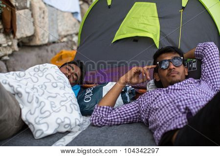 KOS, GREECE - SEP 28, 2015: Unidentified refugees near tents. More than half are migrants from Syria, but there are refugees from other countries -Afghanistan, Pakistan, Iraq, Iran, Mali, Eritrea.