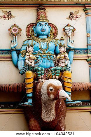 Lord Vishnu along with his wife seated on his vehicle Garuda