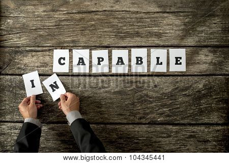 Overhead View Of Personal Motivator Or Consultant Removing Letters In From The Word Incapable
