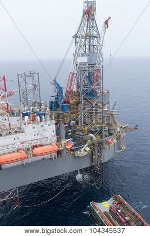 Aerial View Of Offshore Jack Up Drilling Rig And Supply Vessel In The Middle Of The Ocean