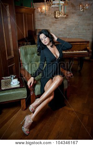 Beautiful sexy girl sitting on chair and relaxing. Portrait of brunette woman with long legs posing