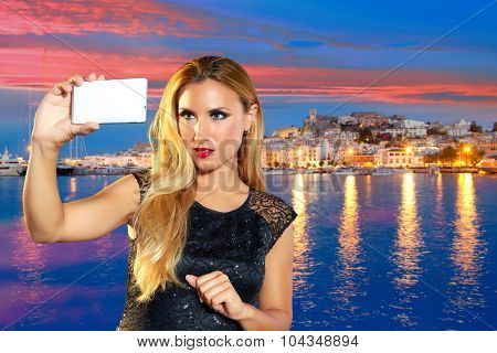 Blond tourist girl taking selfie photo in Ibiza skyline at sunset photomount
