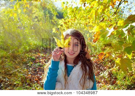 Autumn kid girl relaxed in fall forest with leaves