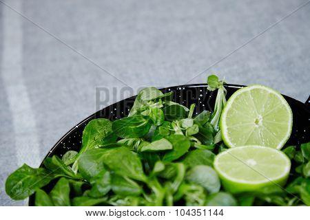 Watercress Salad Wit Half Split Lime In Wok Black Bowl Close Up On Rug