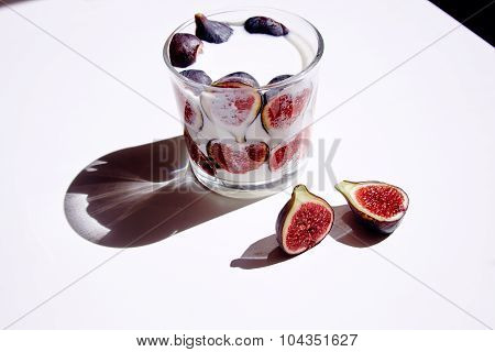 Glass With Milk And Figs; One Half Split Fig On White Table Natural Direct Sunlight