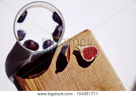 Glass With Milk And Figs; One Half Split Fig On Wood White Table Natural Direct Sunlight Top View