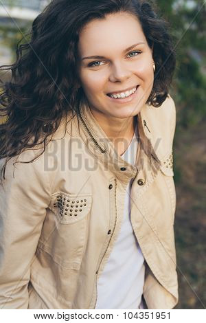 Portrait Of Young Happy Smiling Woman In A Beige Jacket With Rivets Outdoors