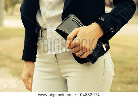 Woman In Jeans, Shirt And A Black Jacket Holding A Purse In Her Hand Outdoors