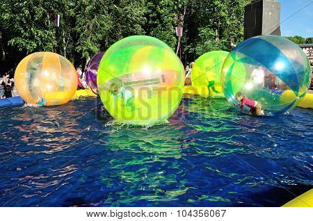 Unidentified Kids Zorb Inside Large Air Balls On Water In The Pool