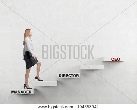 A Young Business Lady Is Going Up The Corporate Ladder From The Manager To Ceo. Concrete Background.