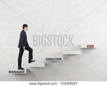 An Ambitious Man In A Suit Is Going Up The Corporate Ladder From The Manager To Ceo. Concrete Backgr