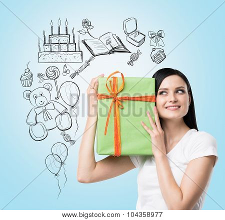 A Brunette Holds A Green Gift Box. Birthday Celebration Sketch Is Drawn On The Light Blue Background