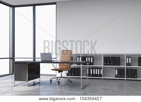 A Workplace In A Modern Corner Panoramic Office With Copy Space In The Windows. A Black Desk With A