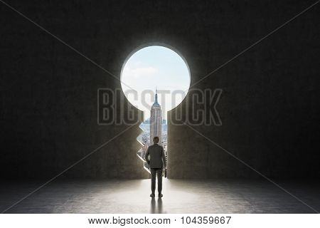 A Keyhole In The Concrete Wall. A Businessman Dressed In Formal Suit Is Looking At New York City In