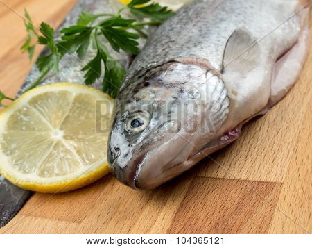 Two raw rainbow trouts on wooden board decorated with parsley and lemon slices