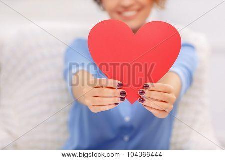 Cheerful girl holding heart