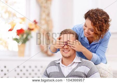 Girl closing eyes of her man
