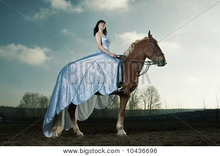 Beautiful Woman Riding On A Brown Horse