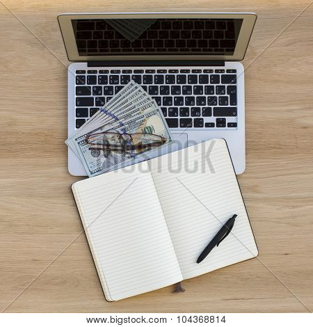 Laptop, dollars bills, and an open notebook with space for your text.