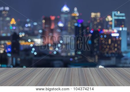Opening wooden floor, blurred bokeh lights of central business park at nigh