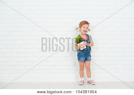 Happy Child Girl Laughing And Holding Pot With Potted Plant Near Brick Wall