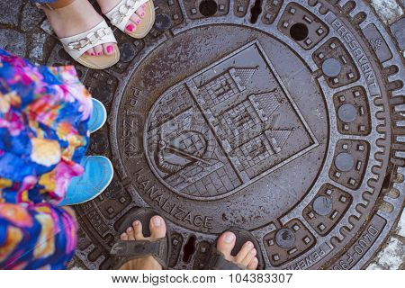 Six legs three people are standing on wet cast iron manhole, Prague