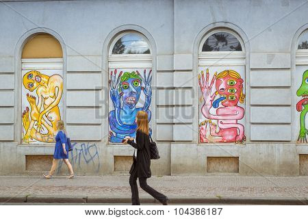 Street art - colorful images of freaks, monsters, aliens in the window bays