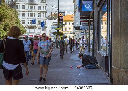 A homeless beggar is begging on a busy street