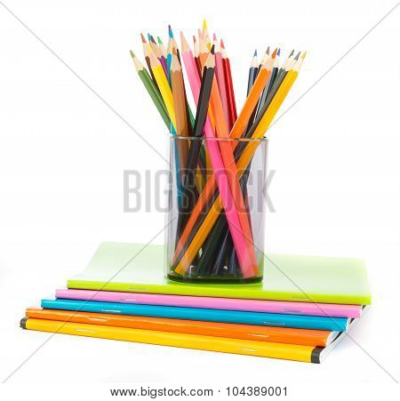 Pencil cup with crayons on exercise books