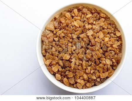 rock sugar made from date palm kept in a bowl on a plain background