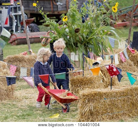 Children Playing With Hay And A Wheel Barrow