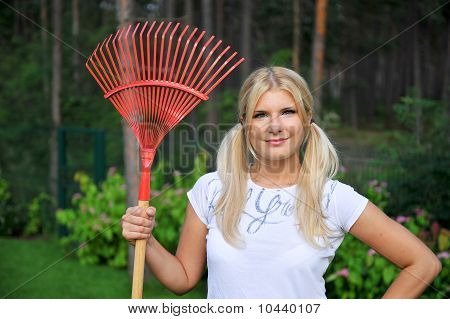 Young Pretty Gardening Woman With Tools And Rakes Outdoors