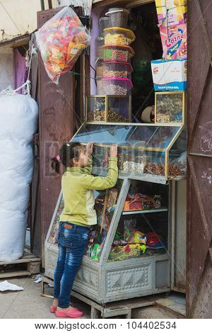 The African Girl Buys Snack From Grocery In Morocco