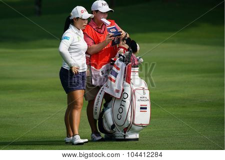KUALA LUMPUR, MALAYSIA - OCTOBER 09, 2015: Thailand's Moriya Jutanugarn discusses with her caddy on the fairway of the KL Golf & Country Club at the 2015 Sime Darby LPGA Malaysia golf tournament.
