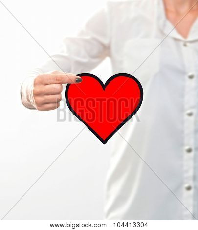 conceptual , woman's hand holding a heart drawing