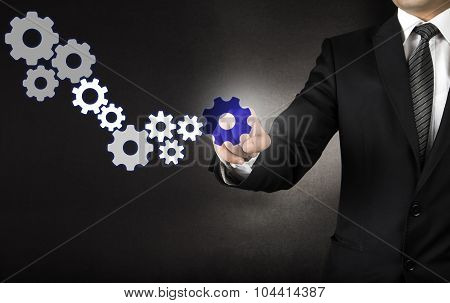 Businessman is touching virtual sprocket