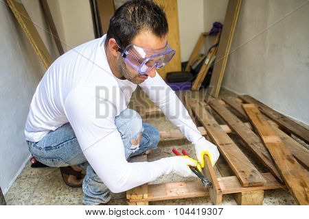 Man Dismantled A Pallet With Hammer And Chisel
