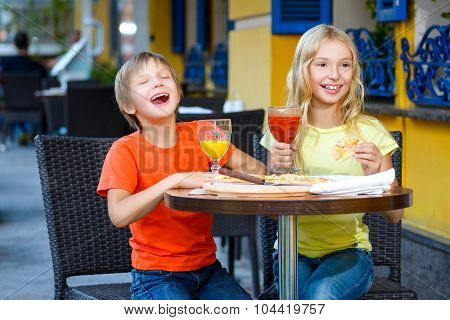 Happy or satisfied boy width girl eating pizza and drinking juice