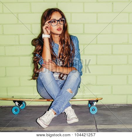 Beautiful Long-haired Lady With A Wooden Skateboard Near A Green Brick Wall
