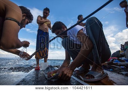 KOS, GREECE - SENT 28, 2015: Unidentified refugees wash clothes on the beach. Kos island is located just 4 kilometers from the Turkish coast, and many refugees come from Turkey in an inflatable boats.
