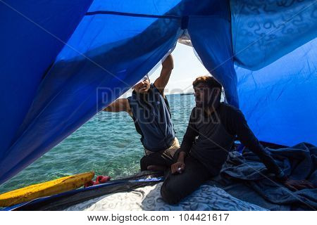 KOS, GREECE - FEB 28, 2015: Refugees in his tent on the waterfront Aegean sea. Kos island is located just 4 km from the Turkish coast, and many refugees come from Turkey in an inflatable boats.