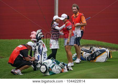 KUALA LUMPUR, MALAYSIA - OCTOBER 09, 2015: Japan's Sakura Yokomine (left) hugs South Korea's Ha Na Jang (right) after completing the day's play at the 2015 Sime Darby LPGA Malaysia golf tournament.