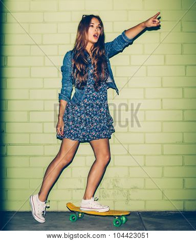 Beautiful Long-haired Lady With A Plastic Penny-board Near A Green Brick Wall