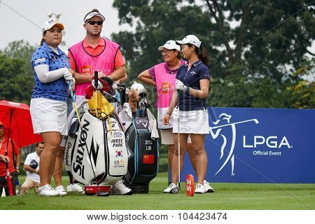 KUALA LUMPUR, MALAYSIA - OCTOBER 10, 2015: Golfers Inbee Park (left) and Xi Yu Lin wait to tee off at the sixth hole of the KL Golf & Country Club at the 2015 Sime Darby LPGA Malaysia golf tournament.