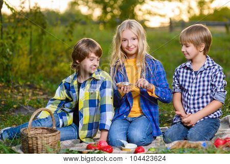 Happy smiling boy and girl lying together on rug. picnic in park concept