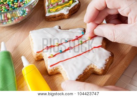 Detail Of Woman's Hand Which Is Decorating Christmas Cookie. Selective Focus