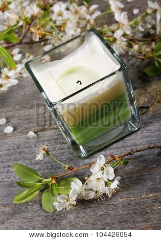 Branches Of A Cherry And A Candle On An Old Table