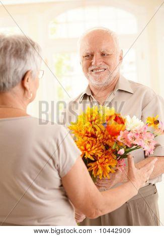 Smiling Senior Man Bringing Flowers