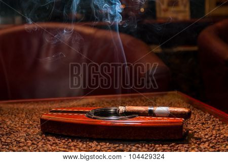A Smoking Expensive Cigars In The Ashtray On The Table