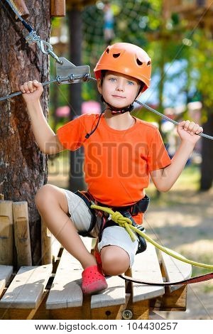 Happy boy having fun when playing at adventure park, holding ropes and sitting on wooden stairs